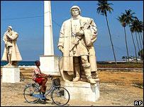 Boy cycles past colonial-era statue, Sao Tome