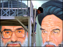 Boy plays in front of portraits of Ayatollah Khamenei (l) and    Ayatollah Khomeini (r)