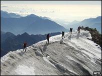 Climbers walk along ridge in Swiss Alps