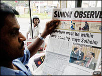 Reader with a Sri Lankan newspaper