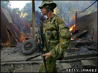Australian soldier and burning house, Dili, June 2006