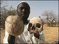 Darfur villager shows skulls from mass grave