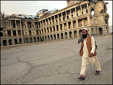 Man waslk past ruined royal palace in Kabul